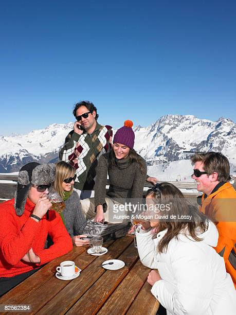 group of friends having drink on terrace - meribel stock photos and pictures