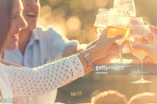 Grupo de amigos con bebidas en la puesta de sol.