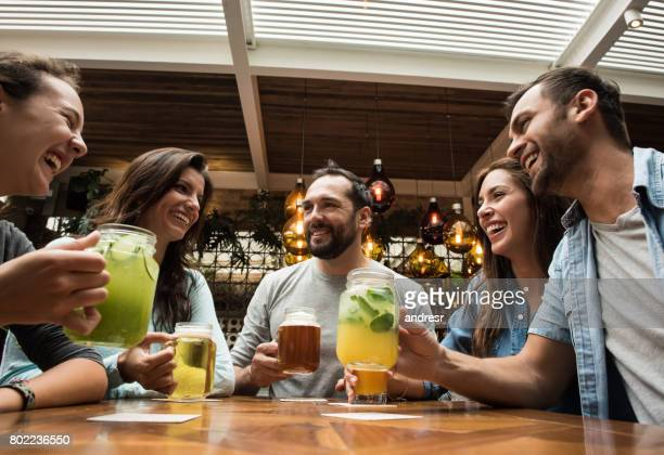 group of friends having drinks at the bar - cocktail party stock pictures, royalty-free photos & images