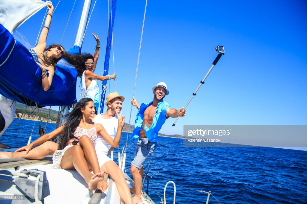 Group of friends having fun and making selfie on yacht : Stock Photo