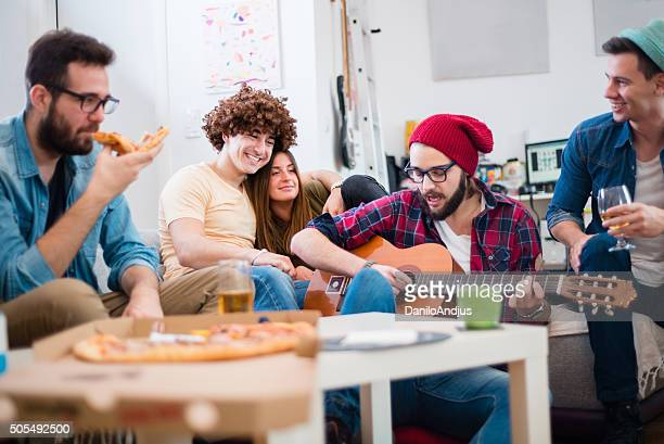 group of friends having fun and playing guitar