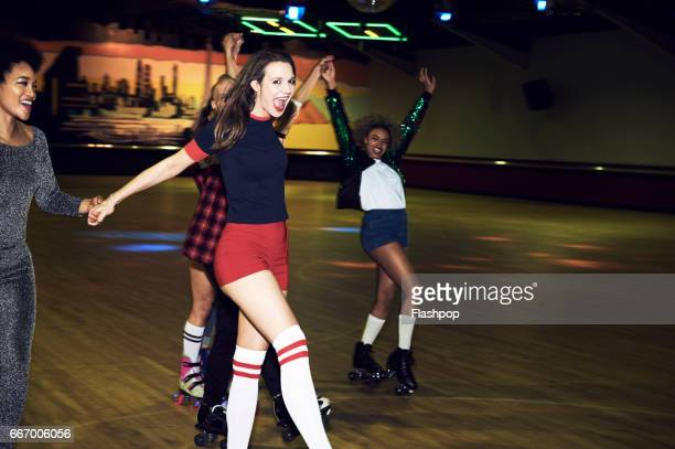 group of friends having fun at roller disco - roller rink stock photos and pictures