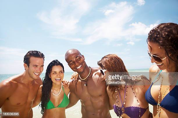 Group of friends having fun on beach during vacation
