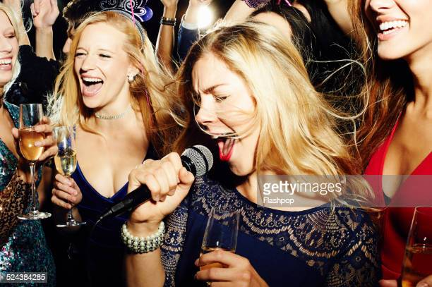 group of friends having fun on night out. karaoke. - singing stock pictures, royalty-free photos & images