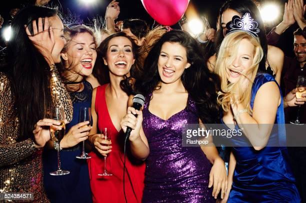 Group of friends having fun on night out. Karaoke.