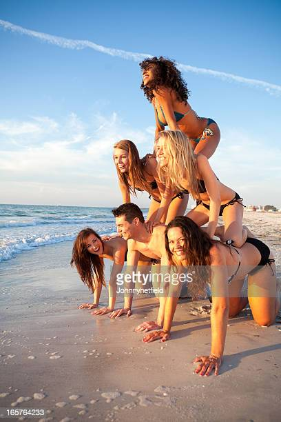group of friends having fun on the beach - human pyramid stock photos and pictures