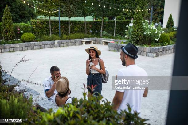 a group of friends having fun outdoors on a summer evening - ambient light stock pictures, royalty-free photos & images