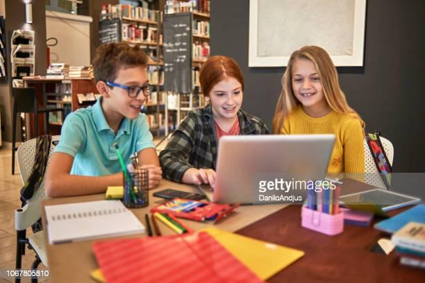 groep vrienden met plezier samen studeren in de bibliotheek - 10 11 jaar stockfoto's en -beelden