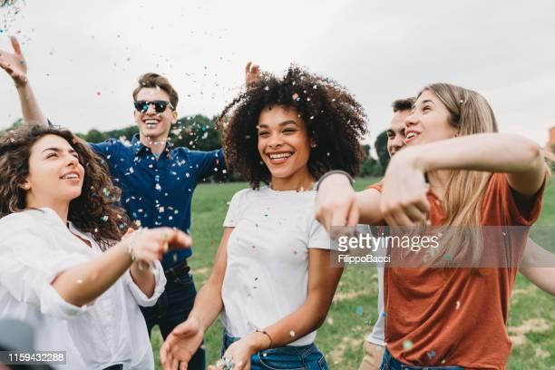 groep vrienden met plezier samen op het park met confetti - public park stockfoto's en -beelden