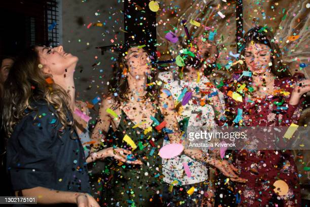 group of friends having fun with confetti at home. - after party stock pictures, royalty-free photos & images