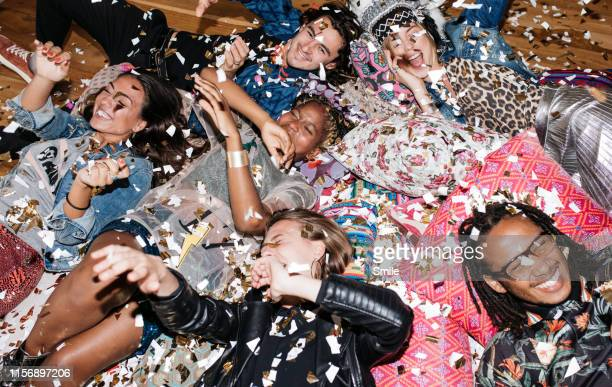 group of friends having fun with confetti on the floor - party stock-fotos und bilder