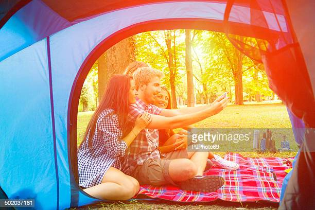 Group of friends having fun with smartphone at camping