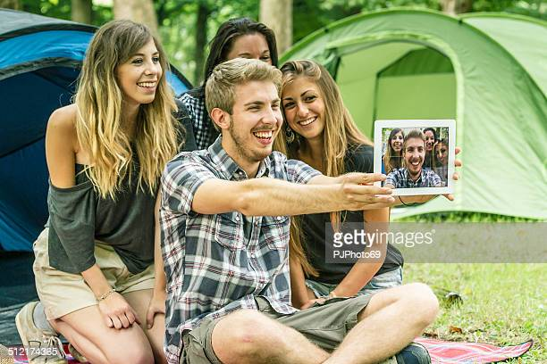 group of friends having fun with tablet at camping - pjphoto69 stock pictures, royalty-free photos & images