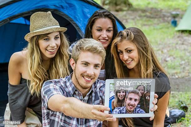 gruppe von freunden, die spaß mit tablet beim camping - pjphoto69 stock-fotos und bilder