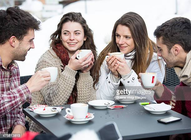 Group of friends having hot drinks in  snow