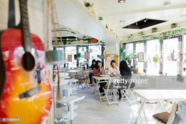group of friends having lunch in cafe - wide angle stock pictures, royalty-free photos & images