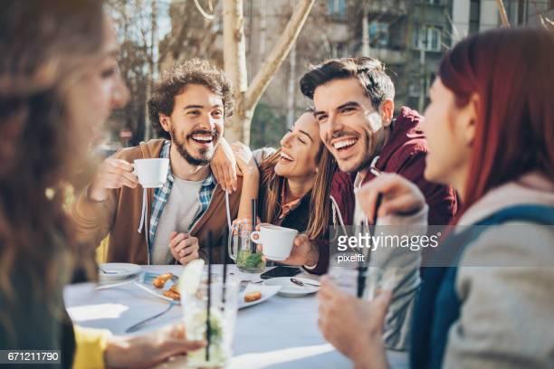 Grupp av vänner som har lunch utomhus