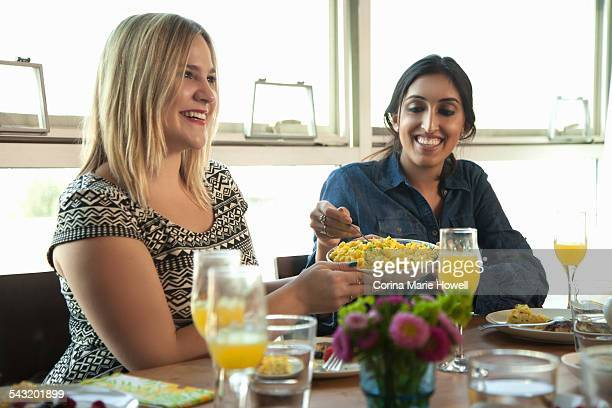 Group of friends having meal at table, young woman passing plate to friend