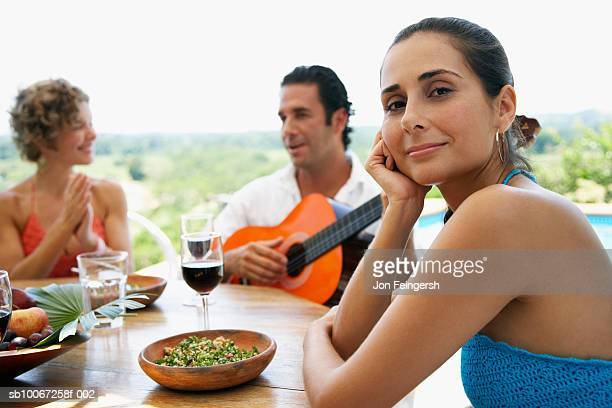 group of friends having meal on patio, man playing guitar - woman sitting on man's lap stock pictures, royalty-free photos & images
