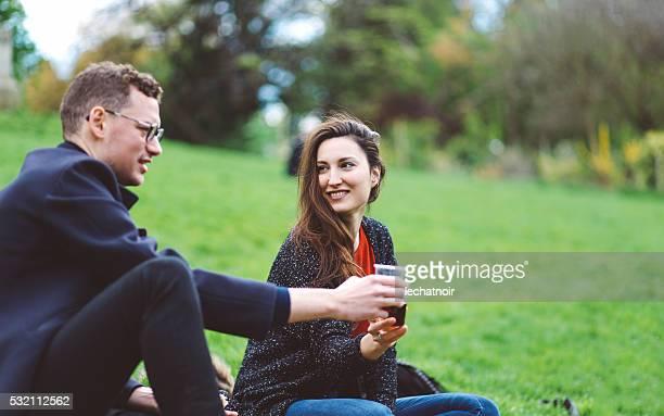 Group of friends having picnic in Parc des Buttes Chaumont
