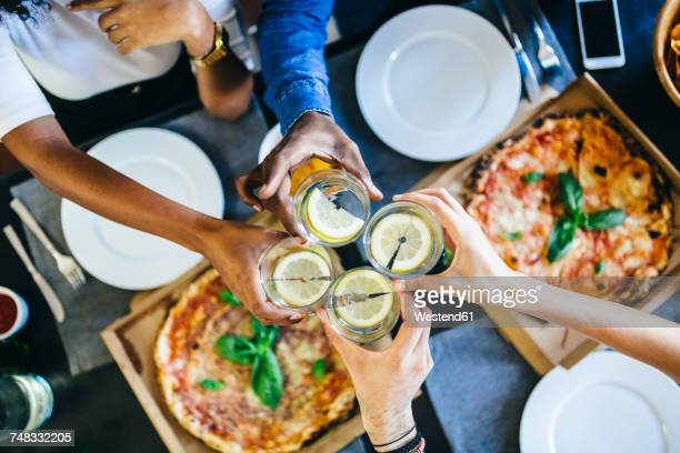 Group of friends having pizza and clinking glasses of water at home