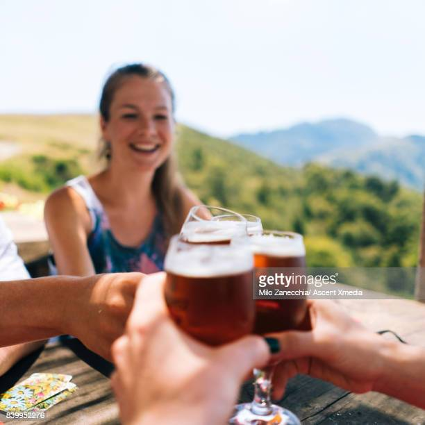 Group of friends hold up beer glasses to cheers