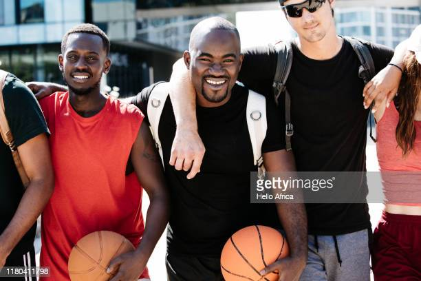 Group of friends holding basketballs standing with arms around each other