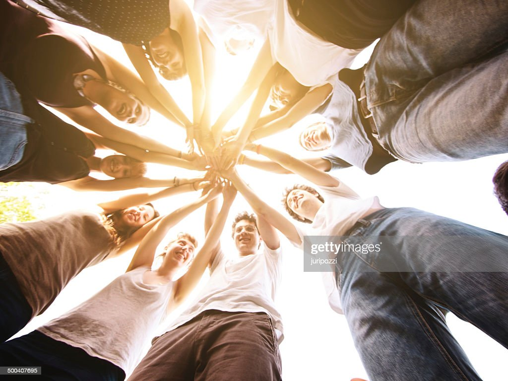 Group of friends holding hands together making a circle : Stock Photo