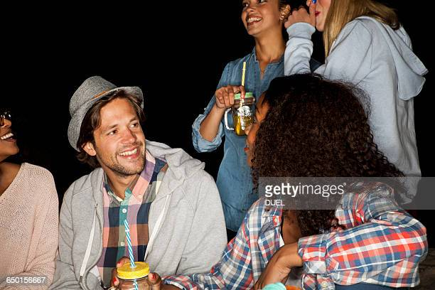 Group of friends holding mason jars chatting and smiling