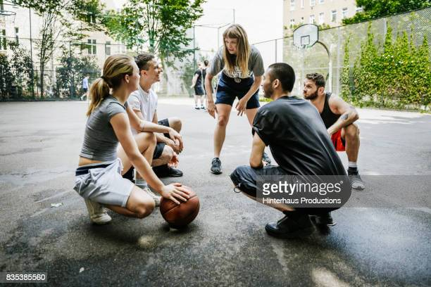 group of friends huddled together talking about basketball tactics. - sportmannschaft stock-fotos und bilder