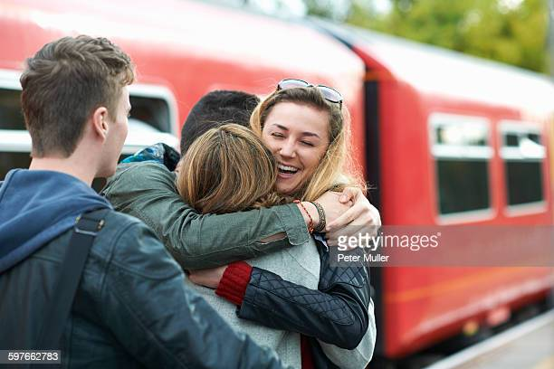 Group of friends hugging at railway station, smiling