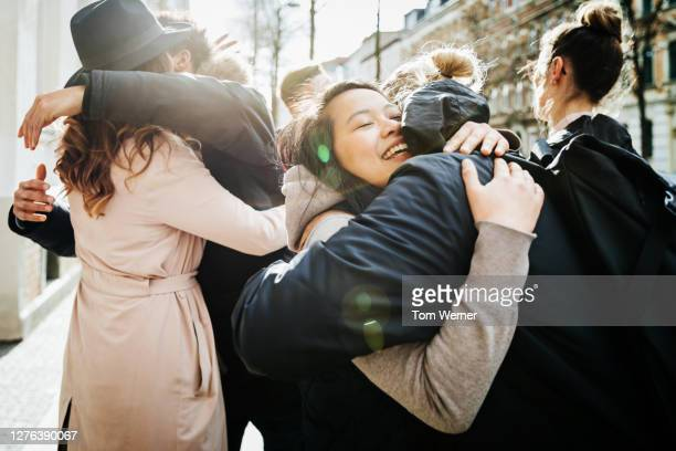 group of friends hugging in street - embracing stock pictures, royalty-free photos & images