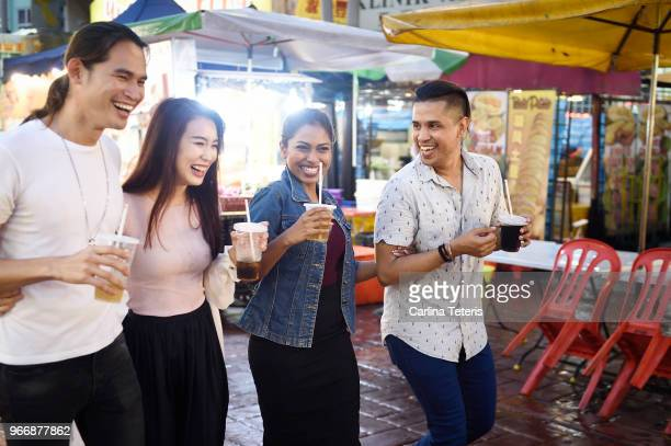 group of friends in a malaysian night market - malaysian culture stock pictures, royalty-free photos & images