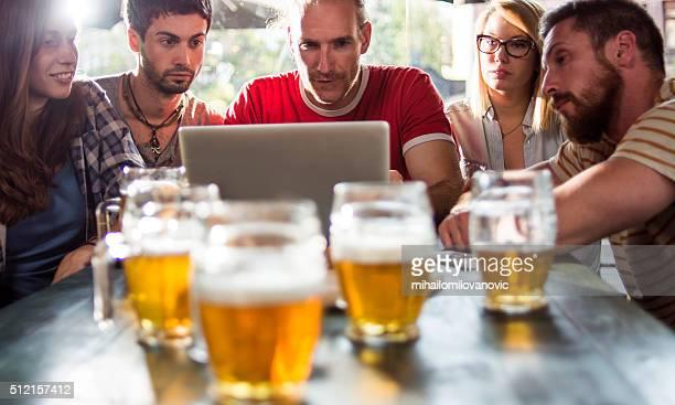 eine gruppe von freunden in einem kneipe schaut an einen laptop - mihailomilovanovic stock-fotos und bilder