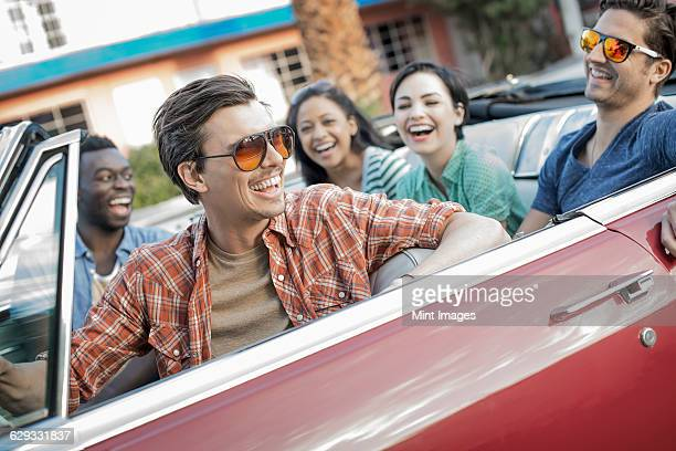 A group of friends in a red convertible car on a road trip.