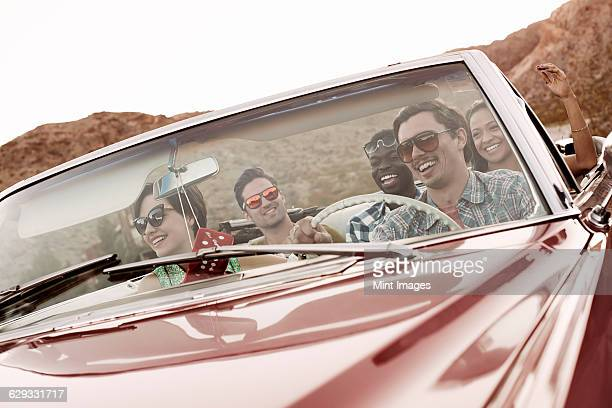 A group of friends in a red open top convertible classic car on a road trip.