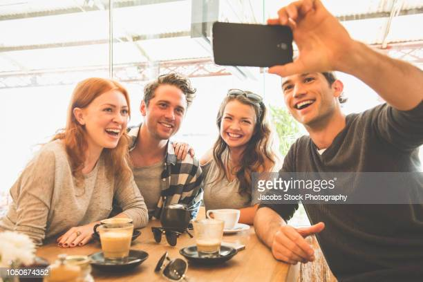 group of friends in cafe - mid adult stock pictures, royalty-free photos & images