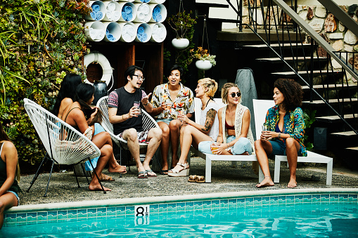 Group of friends in discussion during party by pool hotel - gettyimageskorea