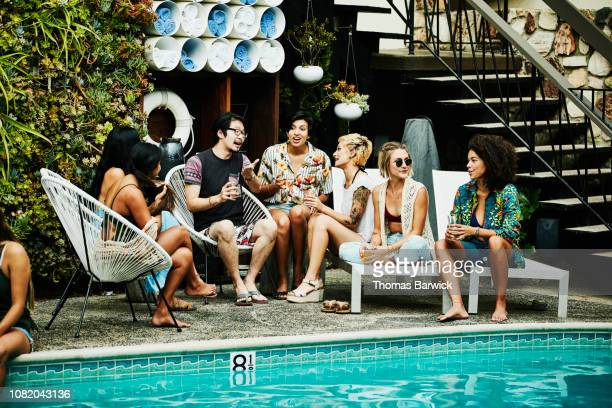 group of friends in discussion during party by pool hotel - pool party stock pictures, royalty-free photos & images