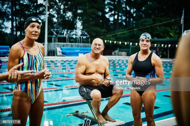 group of friends in discussion on outdoor pool deck before early morning workout - 50 59 jaar stockfoto's en -beelden