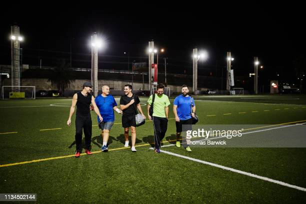 group of friends in discussion while walking off soccer field after nighttime game - cinq personnes photos et images de collection
