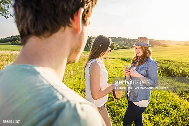 Group of friends in field, young woman using smartphone