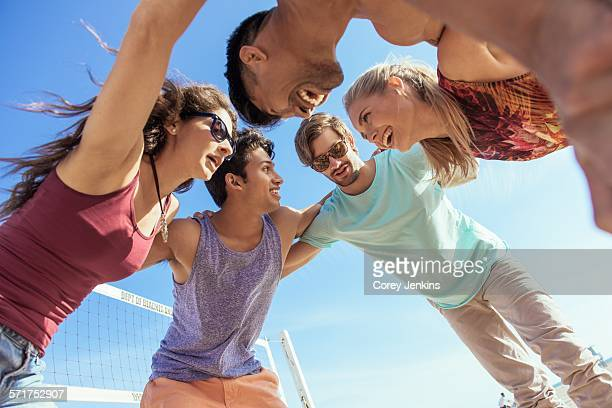 Group of friends in huddle on beach, low angle view