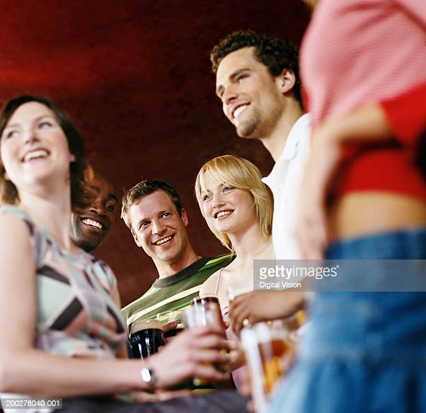 Group of friends in pub holding drinks, smiling, low angle view