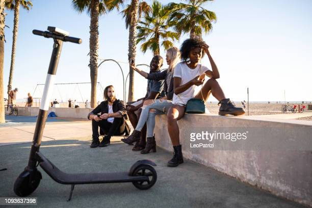 group of friends in santa monica - los angeles - have fun during a vacation - mobility scooter stock photos and pictures