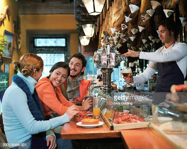 group of friends in tapas bar - tapas stock photos and pictures