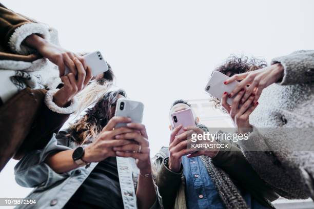 group of friends in the street with smartphone - facebook stock pictures, royalty-free photos & images
