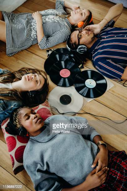 group of friends intently listening to vinyls whilst lounging on the floor - house after party stock pictures, royalty-free photos & images