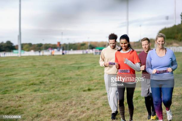 group of friends jogging at outdoor charity event - competition group stock pictures, royalty-free photos & images