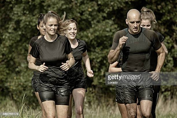 group of friends jogging outdoors during mud run